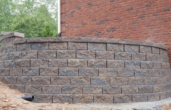 retaining wall by a red-brick house
