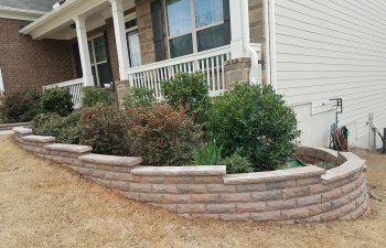 retaining walls surrounding plants in front of a house