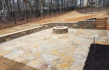 flagstone patio with a fire pit and retaining walls